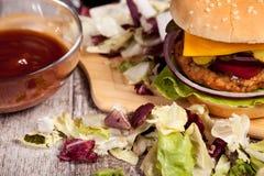 Закройте вверх очень вкусного домашнего сделанного бургера на деревянной плите Стоковые Фотографии RF