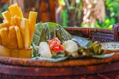 Закройте вверх очень вкусной типичной амазонской еды, зажаренной рыбы сваренной в лист с юккой и подорожнике, шаре салата и Стоковое Фото