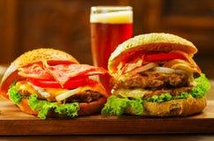 Закройте вверх 2 очень вкусных гамбургеров с говядиной, беконом, луком, томатом, салатом и сыром с стеклом пива позади дальше Стоковое Изображение