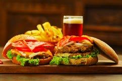Закройте вверх 2 очень вкусных гамбургеров с говядиной, беконом, луком, томатом, салатом и сыром с запачканным стеклом пива Стоковое Изображение
