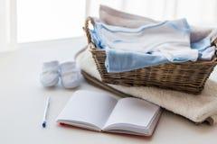 Закройте вверх одежд младенца для newborn и тетради Стоковая Фотография RF