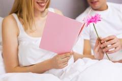 Закройте вверх пар в кровати с открыткой и цветком Стоковая Фотография RF
