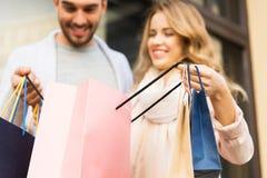 Закройте вверх пар с хозяйственными сумками на улице Стоковое Фото