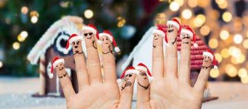 Закройте вверх пальцев с smiley в шляпах santa Стоковое Изображение RF