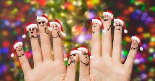 Закройте вверх пальцев с smiley в шляпах santa Стоковое Фото