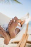 Закройте вверх песочных ног женщины спать в гамаке Стоковые Изображения