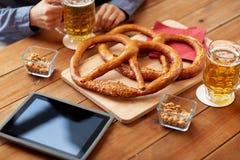 Закройте вверх пива человека выпивая с кренделями на пабе Стоковая Фотография
