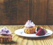 Закройте вверх пирожного пинка клубники на белой плите на деревянной предпосылке Стоковые Изображения