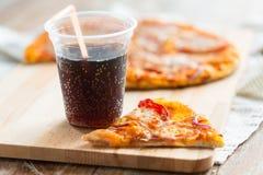 Закройте вверх пиццы с кока-колой на таблице Стоковые Фотографии RF
