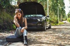 Закройте вверх потревоженной женщины сидя в земле используя ее мобильный телефон и нося sunglases в ее голове, черной футболке и Стоковое Фото