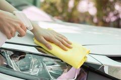 Закройте вверх по автомобилю чистки руки женщины микро- тканью волокна Стоковые Изображения