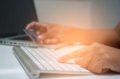 Закройте вверх по азиатскому молодому человеку используя компьтер-книжку и держащ wi кредитной карточки Стоковые Фото