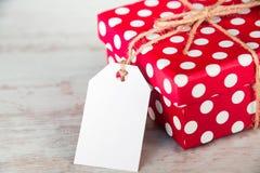 Закройте вверх подарочной коробки поставленной точки красным цветом над белой деревянной предпосылкой пустое примечание Стоковые Изображения
