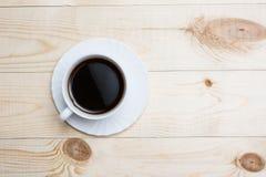 Закройте вверх по белой кофейной чашке на деревянном столе Стоковое Изображение