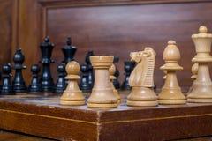 Закройте вверх по белым и черным figurines шахмат на шахматной доске Стоковые Фото
