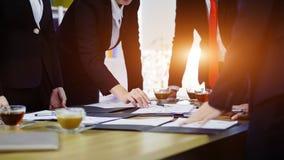 Закройте вверх по бизнесменам группы съемки указывая ручка на документ дальше стоковое изображение