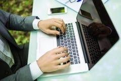 Закройте вверх по бизнесмену на компьтер-книжке на руках таблицы офиса в зеленом Forest Park владение домашнего ключа принципиаль Стоковые Изображения
