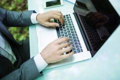 Закройте вверх по бизнесмену на компьтер-книжке на руках таблицы офиса в зеленом Forest Park владение домашнего ключа принципиаль Стоковые Фотографии RF