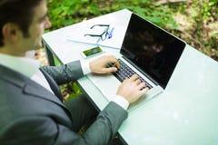 Закройте вверх по бизнесмену портрета на компьтер-книжке на руках таблицы офиса в зеленом Forest Park владение домашнего ключа пр Стоковая Фотография