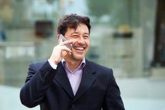 Закройте вверх по бизнесмену усмехаясь и говоря на мобильном телефоне в городе Стоковые Фото