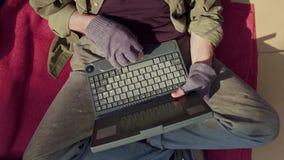 Закройте вверх по взгляду бездомного человека сидя на картоне печатая на компьтер-книжке акции видеоматериалы