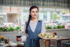 Закройте вверх по взгляду блюд сервировки кельнера на ресторане стоковое фото