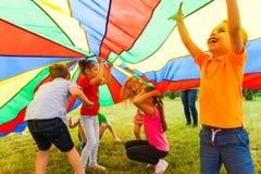 Закройте вверх по взгляду детей под огромной крышкой радуги стоковая фотография rf