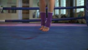 Закройте вверх по взгляду женских ног в носках скача с прыгая веревочкой внутри боксерского ринга в фитнес-клубе Slowmotio сток-видео