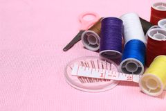 Закройте вверх по взгляду, игле, scissor, проденьте нитку, метр портноя, на розовой предпосылке стоковые изображения