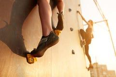 Закройте вверх по взгляду ног женщины в взбираясь ботинках на искусственной стене утеса на заходе солнца 2 активных sporty женщин Стоковое Изображение