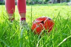 Закройте вверх по взгляду ног ` s девушки и красного шарика на зеленой траве Дети играя концепцию футбола тренировки Стоковое Изображение RF