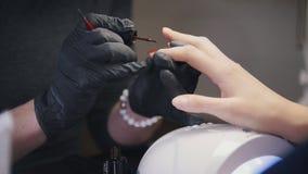 Закройте вверх по взгляду полируя ногтей - женщина получает профессиональный маникюр в салоне красоты стоковая фотография