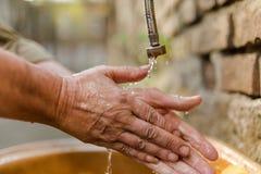 Закройте вверх по взгляду рук бездомного человека моя под проточной водой, Стоковое фото RF