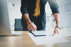 Закройте вверх по взгляду человека в официально носке работая с портативным планшетом и планами чертежей цифровыми в современное  Стоковые Фото