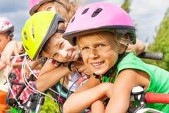 Закройте вверх по взгляду белокурых девушки и мальчика в шлеме Стоковые Фотографии RF