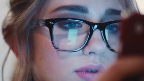 Закройте вверх по взгляду девушки детенышей довольно голубоглазой в винтажных стеклах внимательно используя ее сотовый телефон дл акции видеоматериалы