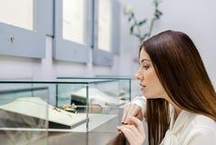 Закройте вверх по взгляду девушки смотря ювелирные изделия в стеклянном случае Стоковая Фотография RF