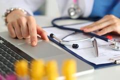 Закройте вверх по взгляду женских рук докторов медицины заполняя пациента m Стоковые Фото