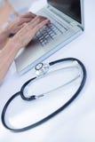 Закройте вверх по взгляду женского доктора используя компьтер-книжку Стоковая Фотография