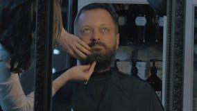 Закройте вверх по взгляду женского парикмахера позаботить о сочная борода человека Парикмахер прикладывая косметики акции видеоматериалы