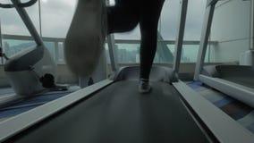 Закройте вверх по взгляду женщины на третбане в центре фитнеса смотря окно с городским пейзажем фарфор Hong Kong сток-видео