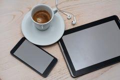 Закройте вверх по взгляду кофе, таблетки и сотового телефона на деревянной предпосылке стоковые фото
