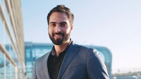 Закройте вверх по взгляду красивого бородатого человека в костюме смотря правый к камере, установке солнечных очков и видеоматериал