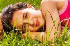 Закройте вверх по взгляду красивой девушки на зеленой траве Стоковое Изображение RF