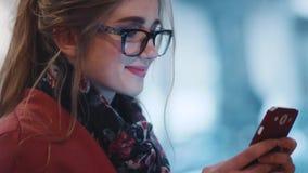 Закройте вверх по взгляду молодой дамы в тормозных стеклах, радостно используя ее телефон Был онлайн, используя wifi сток-видео