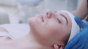 Закройте вверх по взгляду молодой привлекательной женщины с закрытыми глазами, лежащ на таблице cosmetologist's и имеющ пар сток-видео