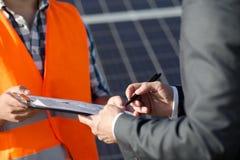 Закройте вверх по взгляду на контракте мастера и клиента sigining на станции солнечной энергии Стоковое фото RF