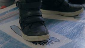 Закройте вверх по взгляду ног мальчика в черных тапках сток-видео