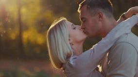 Закройте вверх по взгляду привлекательной молодой белокурой девушки запальчиво целуя ее красивый парня в теплой солнечности осени видеоматериал