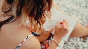 Закройте вверх по взгляду сочинительства женщины в ее дневнике на заходе солнца сидя на пляже видеоматериал
